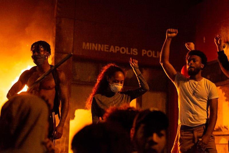 Manifestantes de pie, con los puños levantados, frente a las instalaciones en llamas de la 3ª comisaría de policía de Minneapolis el jueves 28 de mayo de 2020, durante el tercer día de protestas por la muerte de George Floyd en Minneapolis (Steel Brooks/Agencia Anadolu/Getty Images)