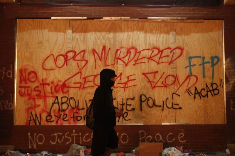 Una persona pasa por delante de un edificio cubierto de graffitis a propósito de la muerte de George Floyd (John Minchillo/AP)