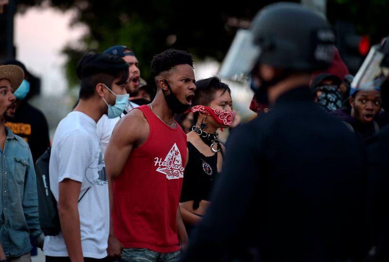 Manifestantes reaccionan frente a la policía al reunirse en el centro de Los Ángeles, el miércoles, para protestar por la muerte de George Floyd.  (Agustín Paullier/AFP/Getty Images)