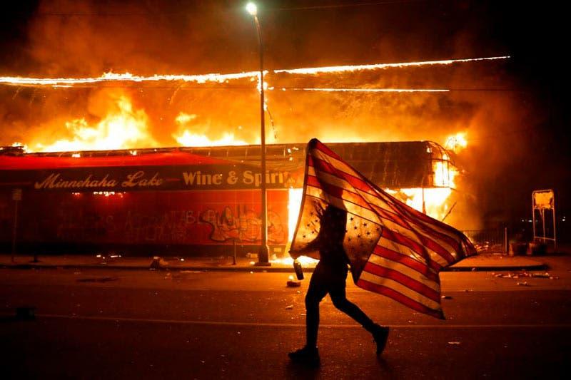 Un manifestante lleva una bandera de EE.UU. al revés, en señal de socorro, junto a un edificio en llamas, el jueves 28 de mayo de 2020, en Minneapolis (AP/Julio Cortez)